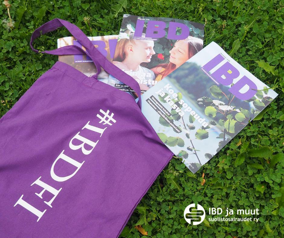 IBD-lehtiä nurmikolla. Nurmella violetti kangaskassi jossa teksti #ibdfi. Oikeassa alakulmassa yhdistyksen logo.